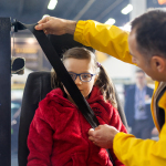 """""""135 cm wzrostu i jazda bez fotelika to śmiertelnie niebezpieczny pomysł"""" - pas bezpieczeństwa biegnie po twarzy dziecka."""
