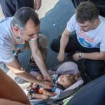 Inspektorzy w pracy z dzieckiem - demonstracja  poprawnego zapięcia dziecka w foteliku.